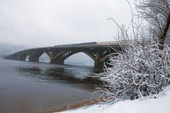 Winter landscape photo. Metrosubway bridge across the Dnipro River at foggy morning. Snow covers tree`s brunches and ground. Snow is starting. Kyiv, Ukraine Stock Photo