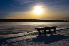 Winter landscape picture in Finland. Empty park bench in front. A frozen lake in the background royalty free stock photo
