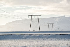 Winter landscape, power lines on a snowy field by the mountains, Iceland Stock Images