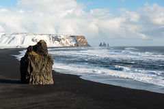 Winter landscape with Reynisdrangar stacks, mountain, black sand beach and ocean waves, Iceland Royalty Free Stock Photos