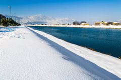 Winter landscape. River flows through city covered with snow Stock Image