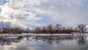 Winter landscape, the river is free of ice. Clouds in the sky, the trees on the shore Royalty Free Stock Photography