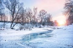 Winter landscape on the river. Near Moscow river Vorya, covered with ice with dark thawed patches, in a snow-covered forest on a frosty sunny evening Stock Images