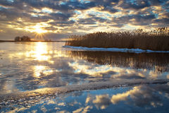 Winter landscape with river, reeds and cloudy sunset sky. Royalty Free Stock Photography
