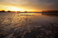 Winter landscape with river, reeds and sunset sky. Stock Photography