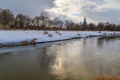 Winter landscape, river, snow-covered shore. The sun through the heavy clouds cold Royalty Free Stock Photo