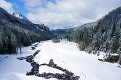Winter landscape. A river of spring runoff in a mountain valley with steep forested slopes Stock Photo