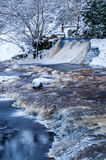 Winter landscape, river under the ice and snow, and tree branches covered with white frost Royalty Free Stock Photos