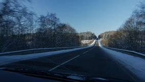 Winter landscape with the road the forest and the blue sky, car point of view stock video footage