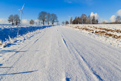 Winter landscape road snow covered fields windmills Royalty Free Stock Photo