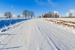 Winter landscape road snow covered fields windmills Stock Photo