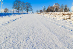 Winter landscape road snow covered fields windmills Stock Photos