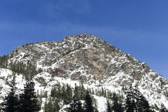 Winter Landscape of Rocky Summit Peak Covered in Powder Snow Above Mountain Forest Stock Photos