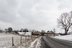 Winter landscape in rural Appalachia. A road leads to an old barn and farmhouse with a pasture to the left and negative space above for copy royalty free stock photo