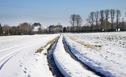 Winter landscape in rural england. English Winter Rural Landscape with track through a snow covered field and Hamlet Royalty Free Stock Images
