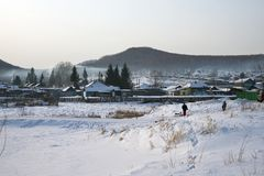A rustic winter landscape with walking children and a frozen river in the foreground. Winter landscape. A rustic winter landscape with walking children and a Royalty Free Stock Image