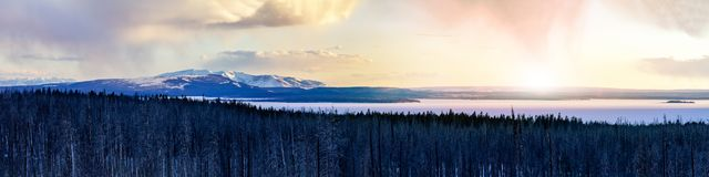 Winter landscape scene in Yellowstone National Park with warm glow of sunlight behind the snow covered mountains. Winter landscape scene in Yellowstone National stock image
