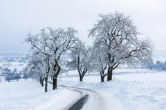 Winter landscape. Slippery snow-covered road between frost-covered trees leads to the village. Winter landscape. Slippery snow-covered road between frost stock photos