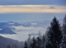 Winter Landscape Slovenia Valley Hills. Beautiful winter landscape in Slovenia with fog in the valley. In the distance you can see church with two bell towers Stock Photo