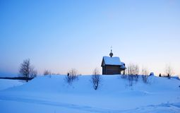 Winter landscape with a small wooden chapel. Royalty Free Stock Image