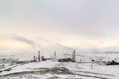 Winter landscape with the smoking pipes of steel works. Gray, cloudy sky. Stock Images