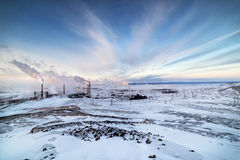 Winter landscape with the smoking pipes of steel works. Royalty Free Stock Photo