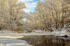 Winter landscape of snow-covered fields, trees and river in the early misty morning Royalty Free Stock Photos