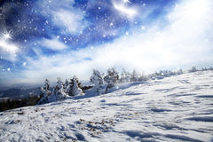 Winter landscape with snow covered hill and blue sky Royalty Free Stock Photography