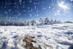 Winter landscape with snow covered hill and blue sky Stock Photography