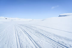 Winter landscape in snow covered mountains. Clear sunny sky with skiing tracks in a winter landscape in snow covered mountains Stock Images