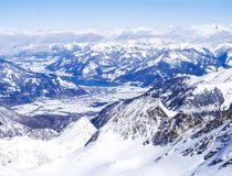 Winter landscape with snow covered slopes and blue sky, with Aerial view of Zell am See lake from the top of. Kitzsteinhorn mountain on . Kaprun ski resort stock images