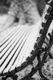 Winter landscape with snow falling and covering bench in English. Winter landscape with snow falling and covering park bench in English countryside Stock Photography