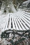 Winter landscape with snow falling and covering bench in English. Winter landscape with snow falling and covering park bench in English countryside Stock Photo