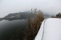 Winter landscape with snow and lake called Lago di Fimon in Nort. Hern Italy photographed by fisheye lens Royalty Free Stock Image