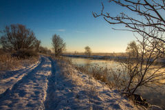 Winter landscape with snow, river, blue sky, road, sunshine, ice. Stock Photo