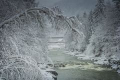 Winter landscape winter snow river. River in the mountains of wood in the snow covered mountains and trees Stock Photo