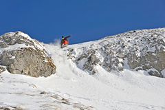 Winter landscape with a snowboarder. A snowboarder jumping off a cliff Stock Photos