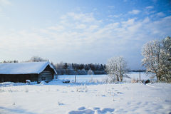 Winter landscape. Snowfield with a forest and house in the distance Stock Images