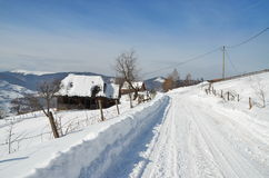Winter landscape with snowy country road and wooden houses. Stock Photos
