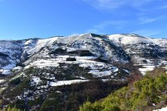 Winter landscape with snowy mountain with trees and small village. Blue sky, Lugo, Galicia, Spain. royalty free stock photography