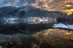 Winter Landscape with Snowy Mountains, Colorful Clouds and Lake Reflection at Sunset