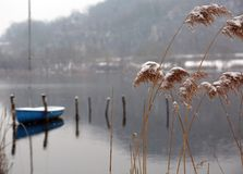 Winter landscape with snowy tufts of grass and the boat moored o royalty free stock photo