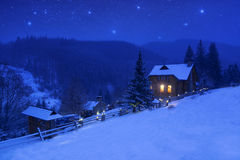 Winter landscape with a starry sky and mountain house Royalty Free Stock Photography