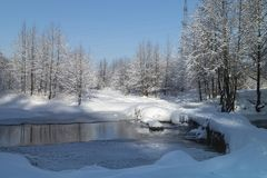 Winter landscape with stream and footbridge in rural terrain royalty free stock photography