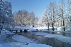 Winter landscape with stream and footbridge in rural terrain royalty free stock photo