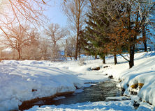 Winter landscape in sunny weather- winter view of rural houses with stream and winter snowdrifts on the foreground Stock Images