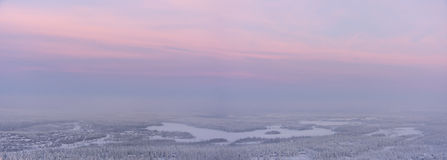 Winter landscape at sunset. A panorama photo of a winter landscape at purple sunset. Between forest there are lot of small huts or houses. The picture is taken Stock Images