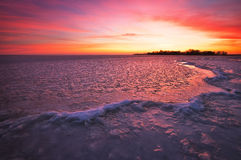 Winter landscape with sunset fiery sky and frozen river. Stock Photo