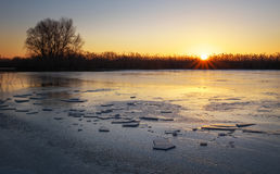 Winter landscape with sunset sky and frozen river. Stock Image