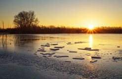 Winter landscape with sunset sky and frozen river. Royalty Free Stock Image